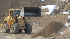 View of wheel loader unloads sand in sandpit. View of wheel loader bulldozer unloads sand in sandpit stock footage