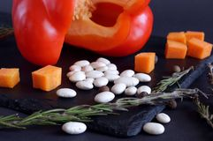 View on white bean grains. Nearby are carrot cubes, and a large, red bell pepper at the back royalty free stock photos