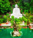 View of white Buddha statue and emerald pond among green trees. At the Linh Ung Pagoda, the Marble Mountains Ngu Hanh Son, Vietnam. The Marble Mountains is a Royalty Free Stock Photo