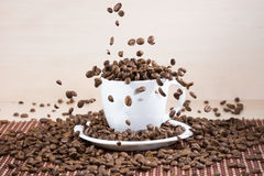 View of white cup standing on white plate with roasted coffee beans on tablemat. Stock Image