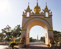 The view of white pagoda of Pratart Phanom temple from the arch Royalty Free Stock Image