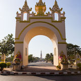The view of white pagoda of Pratart Phanom temple from the arch Royalty Free Stock Images