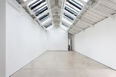 A view of a white painted interior of an empty room or an art gallery with a skylight lighting and concrete floors royalty free stock photography