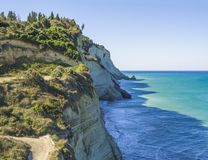View on of white rock steep cliff volcanic bay of Cape Drastis and Peroulades area with tropical deep turquoise clear sea, green stock photography