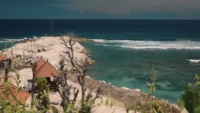 View of white rocky shore and ocean with waves. View of white rocky shore with dead trees and houses with orange roofs and turquoise ocean with waves in south stock footage
