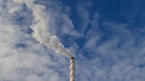View of white smoke from chimney on blue sky background. Ecology and greenhouse effect concept