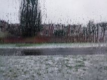 Close up of blurry raindrops on a clear window. View of white snow and sleet outside Stock Images