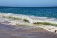 View of White Wave Receding on Perfect Sandy Beach royalty free stock images