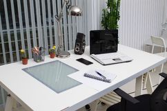View of a white working desk at the office. Computer, camera, mobile phone, notepad and a desk lamp on a white working desk at the office Royalty Free Stock Images