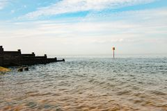 View of Whitstable bay from Whitstable beach. Including the Groynes, Large wooden barriers that split the beach Stock Photo