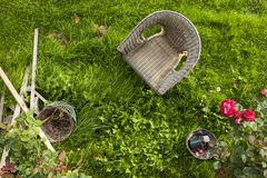 View of a wicker chair in an unkept country garden Royalty Free Stock Photos