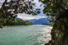View of the wide mountain river off a cliff, overgrown with trees Stock Photo