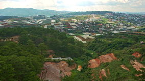 View of Wide Town with Greenhouses Small Buildings among Hills. Upper panorama of wide town with small houses among hills and greenhouses against mountains and stock footage