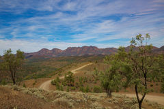 A view of Wilpena Pound. The dirt road goes down the hill towards the mountains Royalty Free Stock Photography