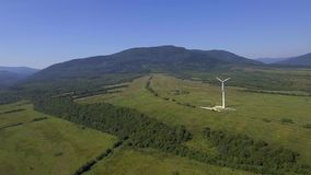 View of wind turbine with mountains in the background. Alternative energy. View of wind turbine with mountains in the background. Alternative energy stock video footage