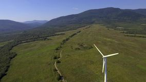 View of wind turbine with mountains in the background. Alternative energy. View of wind turbine with mountains in the background. Alternative energy stock footage