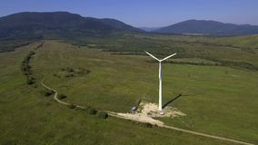 View of wind turbine with mountains in the background. Alternative energy. View of wind turbine with mountains in the background. Alternative energy stock video
