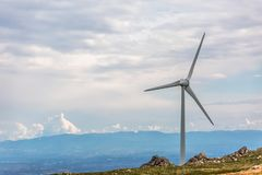 View of a wind turbine on top of mountains, cloudy sky as background. In Portugal environment electricity mill technology environmental nature windmill royalty free stock photos