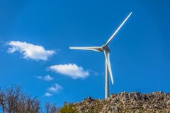 View of a wind turbine on top of mountains. In Portugal environment electricity mill technology environmental nature windmill industry sky energy power royalty free stock image