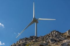 View of a wind turbine on top of mountains. In Portugal environment electricity mill technology environmental nature windmill industry sky energy power royalty free stock images