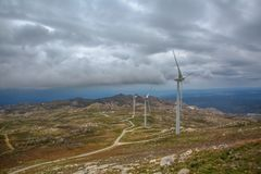 View of a wind turbines on top of mountains, cloudy sky as background. In Portugal environment electricity mill technology environmental nature windmill royalty free stock photography