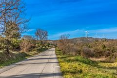 View of a wind turbines on top of mountains. In Portugal road street asphalt trees vegetation landscape environment electricity mill technology environmental royalty free stock image