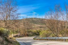 View of a wind turbines on top of mountains. In Portugal road street asphalt trees vegetation landscape environment electricity mill technology environmental royalty free stock photos