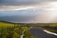 View of windmills power generation against the backdrop of sunset clouds. stock image