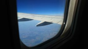 View through the window of the aircraft. The wing of the aircraft against the blue sky and white clouds. Background.  stock video