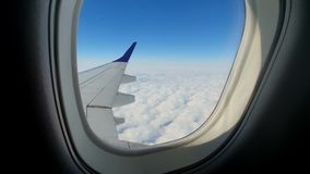 View through the window of the aircraft. The wing of the aircraft against the blue sky and white clouds. Background.  stock footage