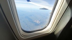 View through the window of the aircraft. The wing of the aircraft against the blue sky and white clouds. Background.  stock video footage