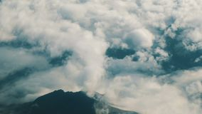 View from the window of an airplane flying over mountains and clouds. stock video footage