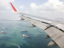 View from the window of the airplane. View from the window of the airplane which above the cargo ship before landing to the Singapore airport.& x28;Blur focus& Royalty Free Stock Photos
