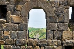 Window in brick wall of the medieval fortress. View through the window in brick wall of the medieval armenian fortress Amberd royalty free stock photography
