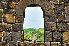 View through the window in brick wall of the medieval fortress. View through the window in brick wall of the medieval armenian fortress Amberd royalty free stock photography
