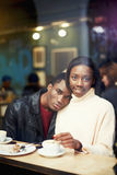 View through window of a charming young woman sitting in cafe with her boyfriend,  dark skinned couple enjoying themselves and goo Royalty Free Stock Photography