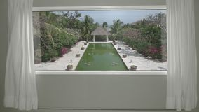 View from the hotel room to calm tropical resort with garden and pool. Background Plate, Chroma Key Video Background. View from the window with curtains to calm stock footage