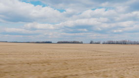View from the window of a fast-moving car. Field early spring - plowed land and blue sky with clouds. Agricultural land stock footage