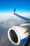 The view from window at flight level, engine and aircraft wing on a blue sky. Stock Photos