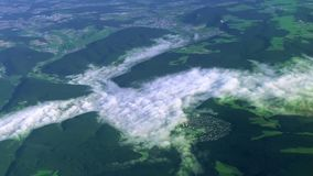 View from a flying plane of clouds and mountains over the Swiss Alps stock footage