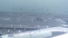 View from window flying airplane over airport and sea. Wing airplane flying above ships in blue ocean. View from stock video footage