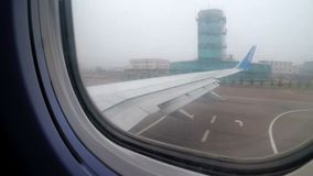 View from the Window of a Jet Passenger Aircraft Maneuvering along the Runway into the Fog. KYIV, UKRAINE, DECEMBER 9, 2017: View from the Window of a Jet stock video footage