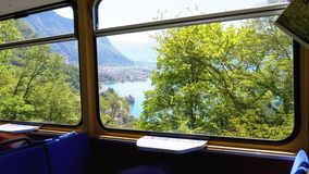 View from window of mountain train on Swiss Village, Montreux City, Lake Geneva, and Alps. stock video footage