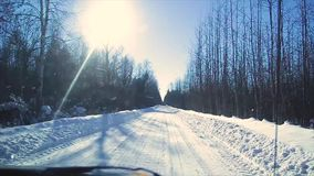 View from the window of a moving car on a winter snowy road through the forest, winter in Russia stock video footage