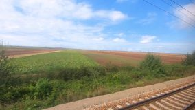 View from window in moving train, railway, fields landscape stock video footage