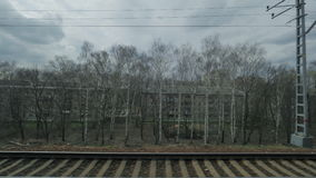 View from the window of a moving train seen trees, buildings, bridges and railroad stock video footage