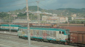 View from the window of a moving train. View on the train station in Milan from the window of a moving train stock footage