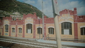 View from the window of a moving train. View on the trailway station in Milan from the window of a moving train stock video footage