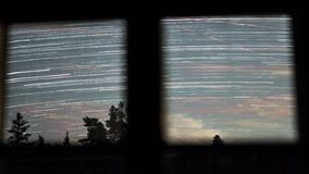 View from the window. Night timelapse footage of star trails in space. Star Trails Night Sky Cosmos Galaxy Time-lapse over old village. Amazing high resolution stock video