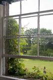 View From the Window. An old sash window, open in spite of the rain, allows a good view out over a traditionally English country garden. The window is stock photos
